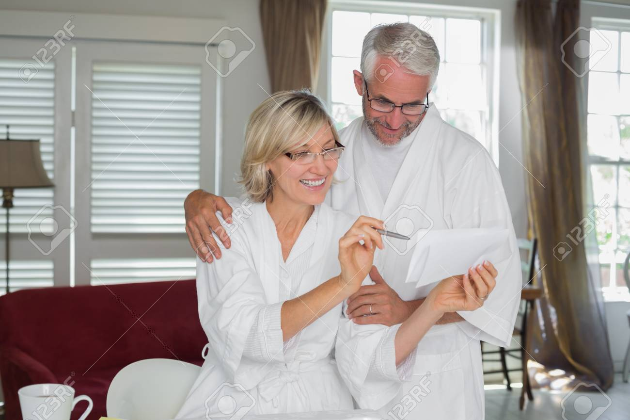 Casual mature couple sitting with bills at home Stock Photo - 28072723