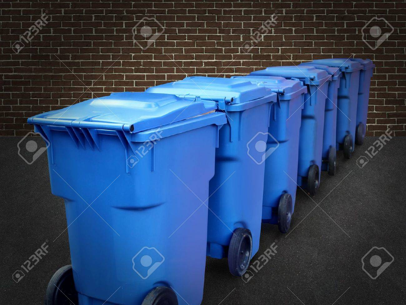 Recycle bins in a group made of commercial size blue plastic containers in a city street back alley against a brick wall as a conservation and recycling symbol of business environmental responsability Stock Photo - 15845981
