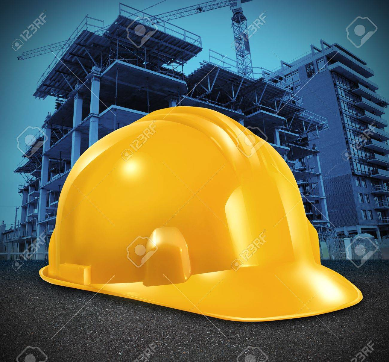 Construction industry and commercial real estate business investment with a yellow builder hard hat and a high rise structure being built as a symbol of economic and financial growth and healthy economy Stock Photo - 16920771