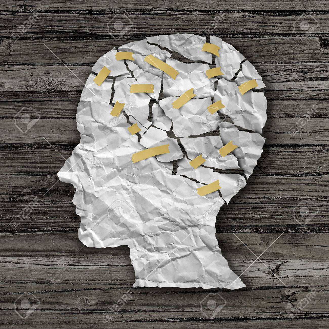 Brain disease therapy and mental health treatment concept as a sheet of torn crumpled white paper taped together shaped as a side profile of a human face on wood as a symbol for neurology surgery and medicine or psychological help. - 33453781