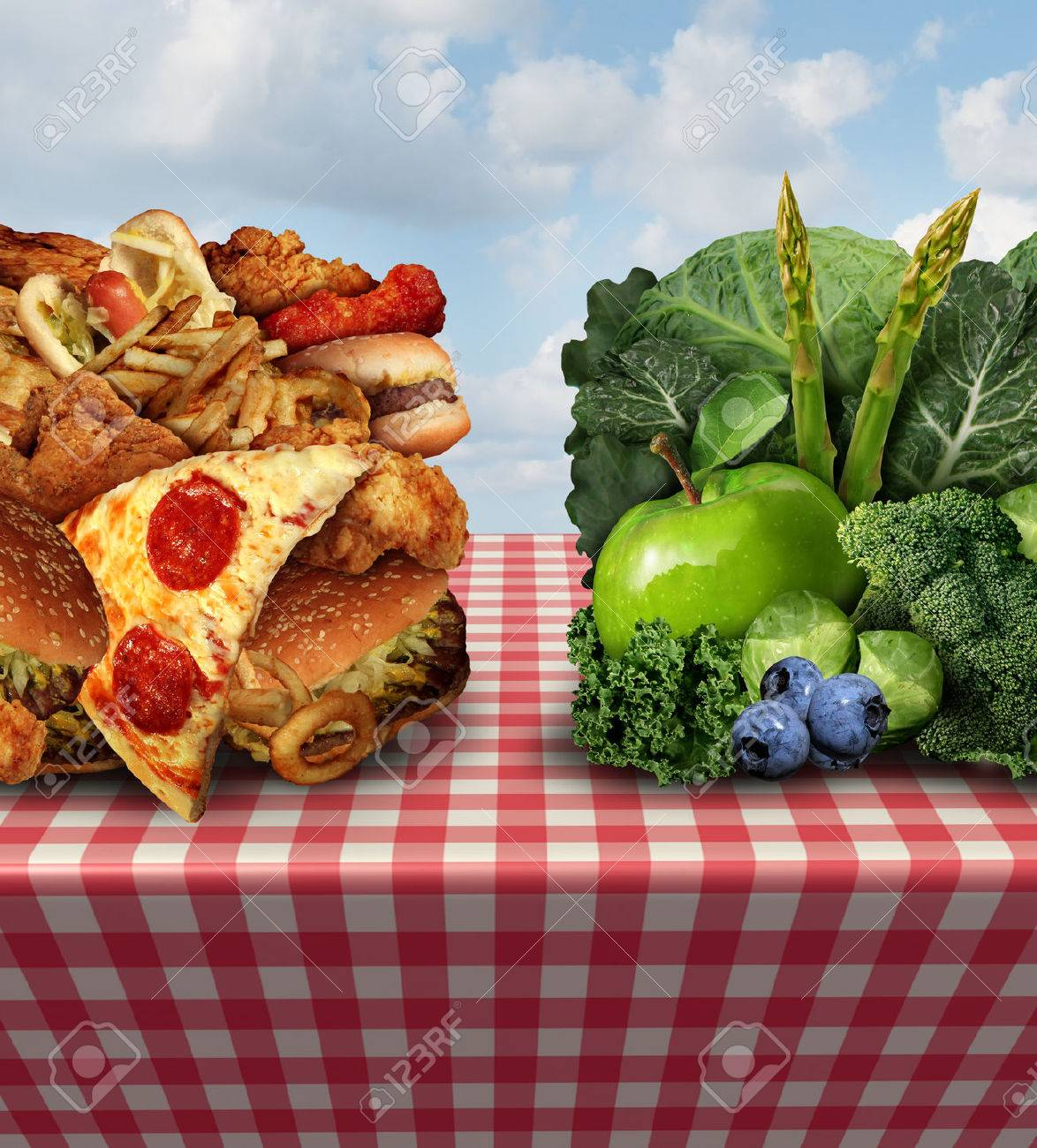 Healthy living concept and diet decision symbol or nutrition choices dilemma between healthy good fresh fruit and vegetables or greasy cholesterol rich fast food on a picnic table with a cloth trying to decide what to eat. - 34185482