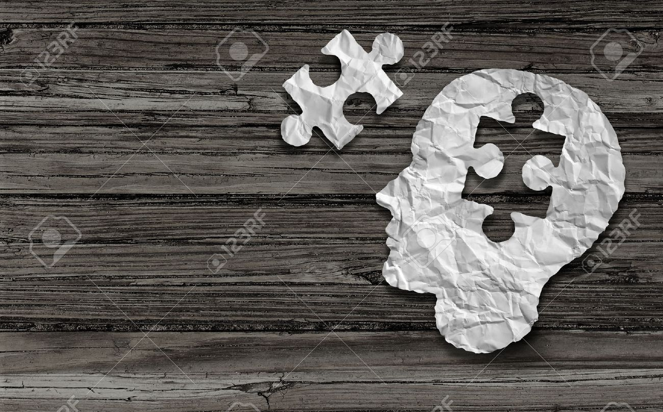 Mental health symbol Puzzle and head brain concept as a human face profile made from crumpled white paper with a jigsaw piece cut out on a rustic old double page spread horizontal wood background. - 39567160