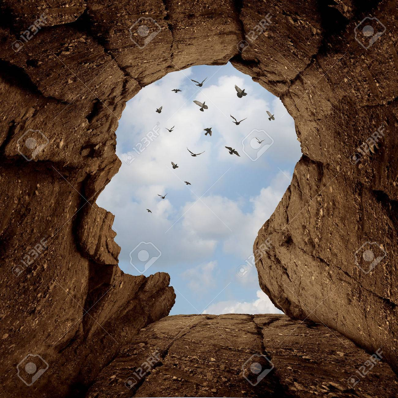 Imagination and discovery concept as a rocky cliff with an opening on top shaped as a human head as a new life metaphor and success motivation symbol with a group of birds flying high in the sky. - 49008348
