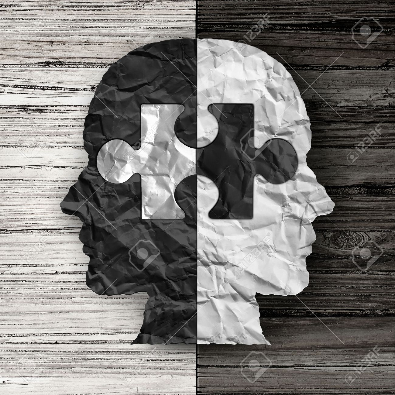 Racial ethnic social issue and equality concept or cultural justice symbol as a black and white crumpled paper shaped as a human head on old rustic wood background with a puzzle piece as a metaphor for social race issues. - 51757389