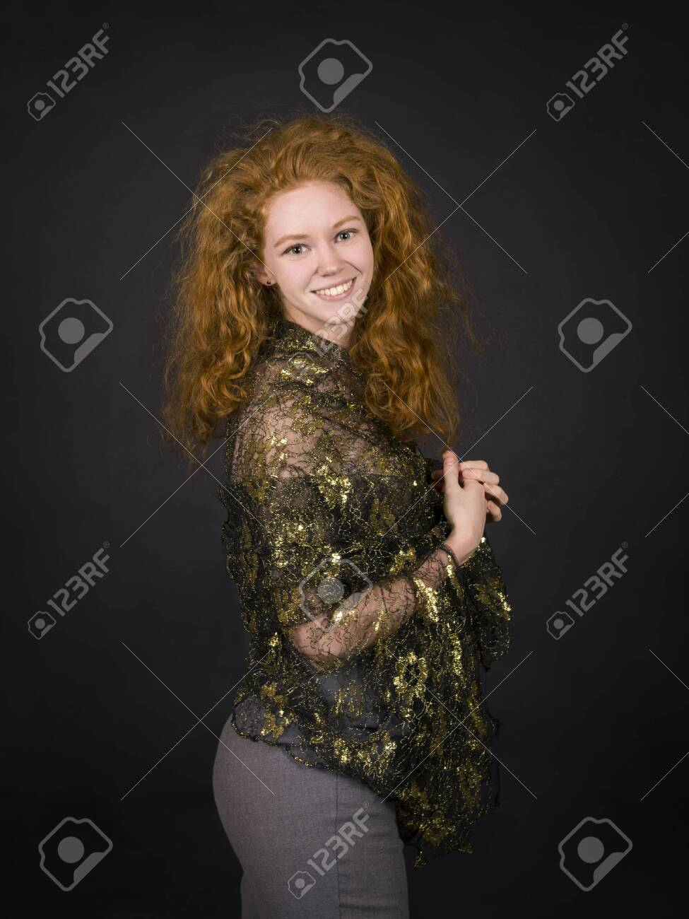 Emotional, red-haired girl in a brocade blouse posing. Studio shooting on a dark background. - 124488667