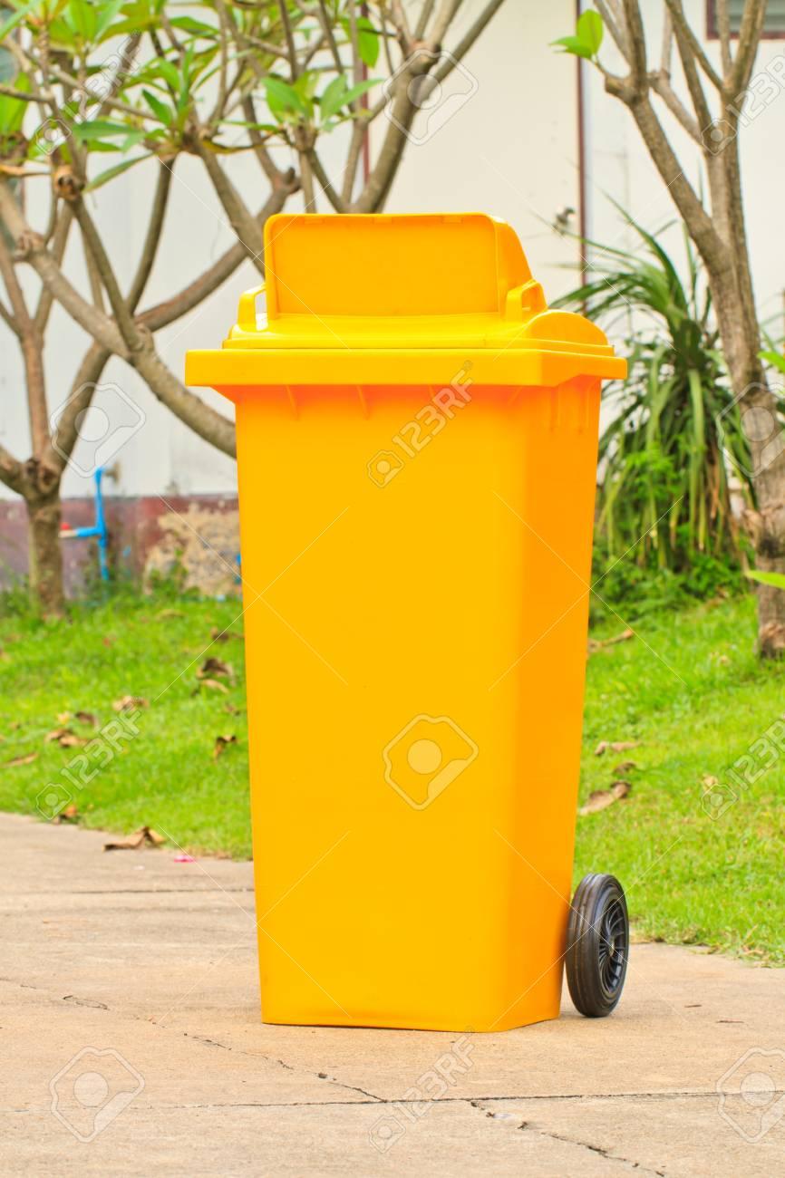 Yellow garbage bin with wheels on road Stock Photo - 16873234