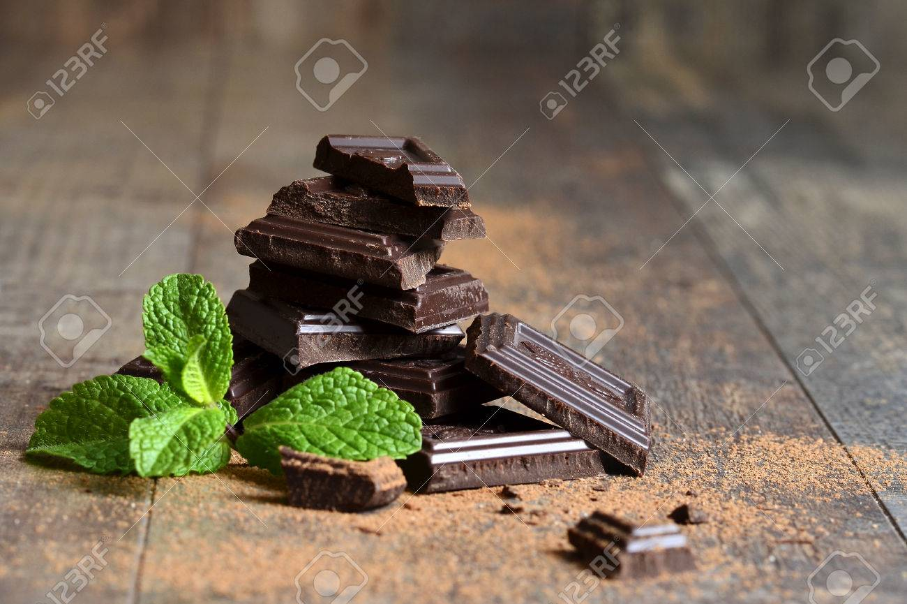 Stack of chocolate slices with mint leaf on a wooden table. - 35649126