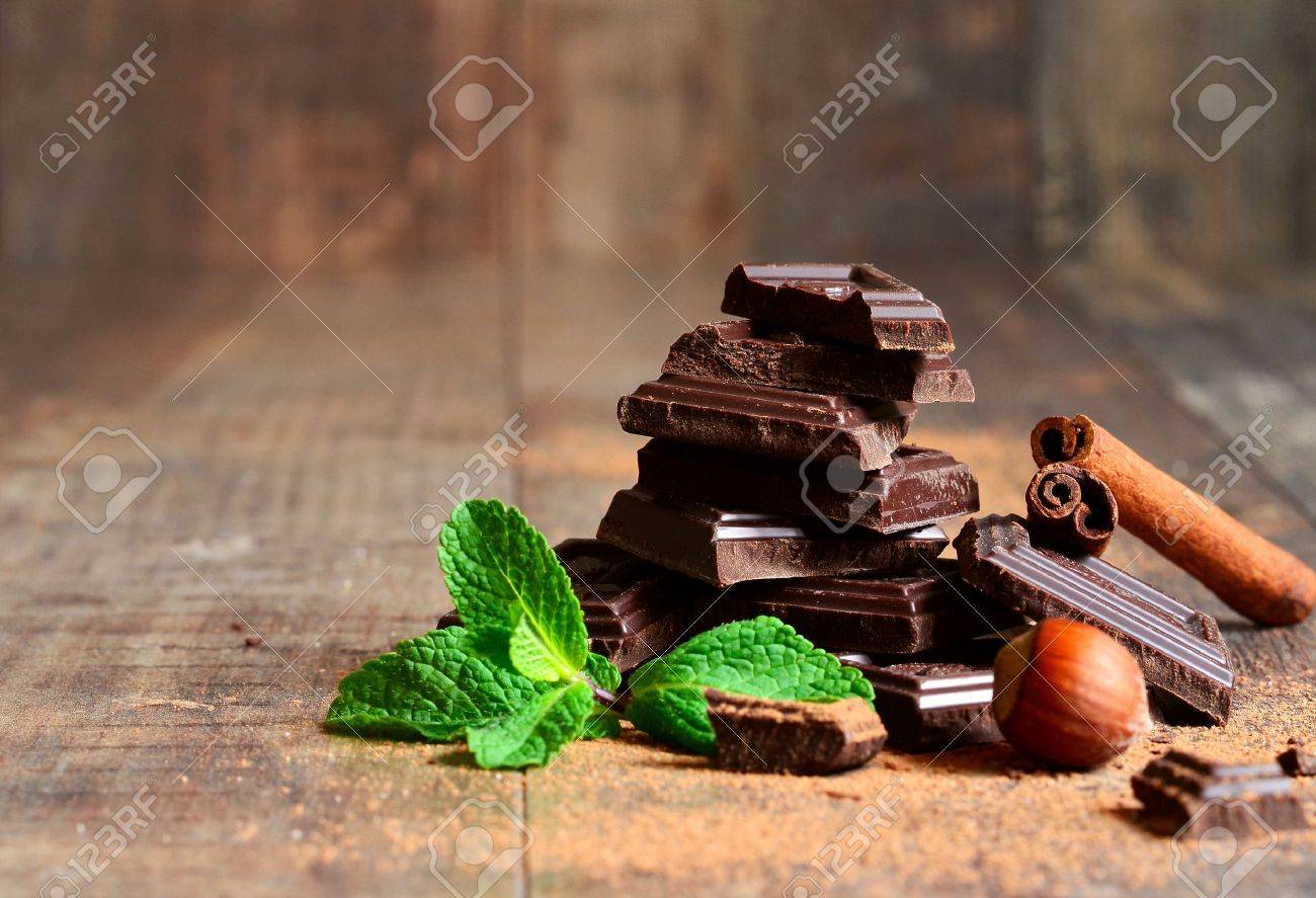Stack of chocolate slices with mint leaf,hazelnut and cinnamon on a wooden table. - 38199064