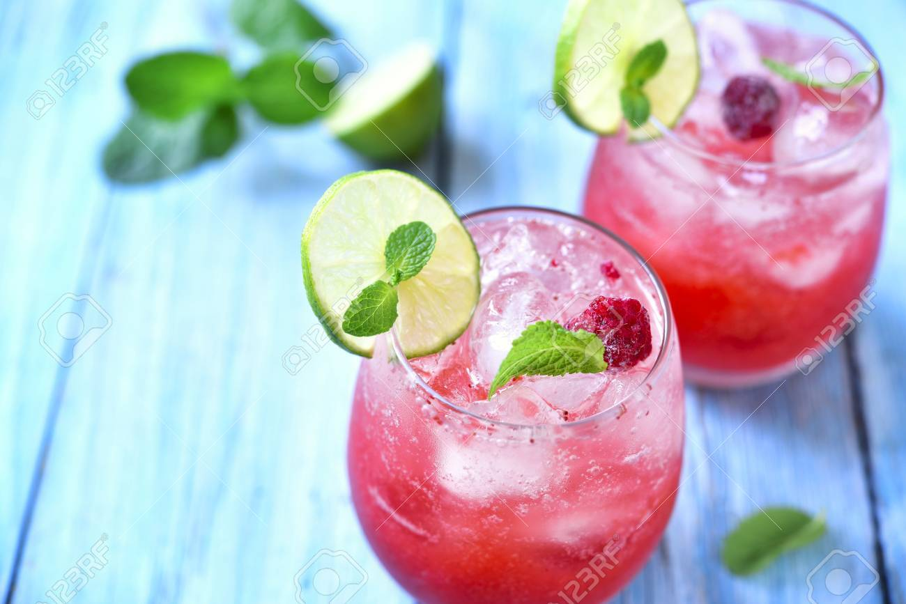 Raspberry lemonade with lime in a glass on a blue wooden background. - 51622103