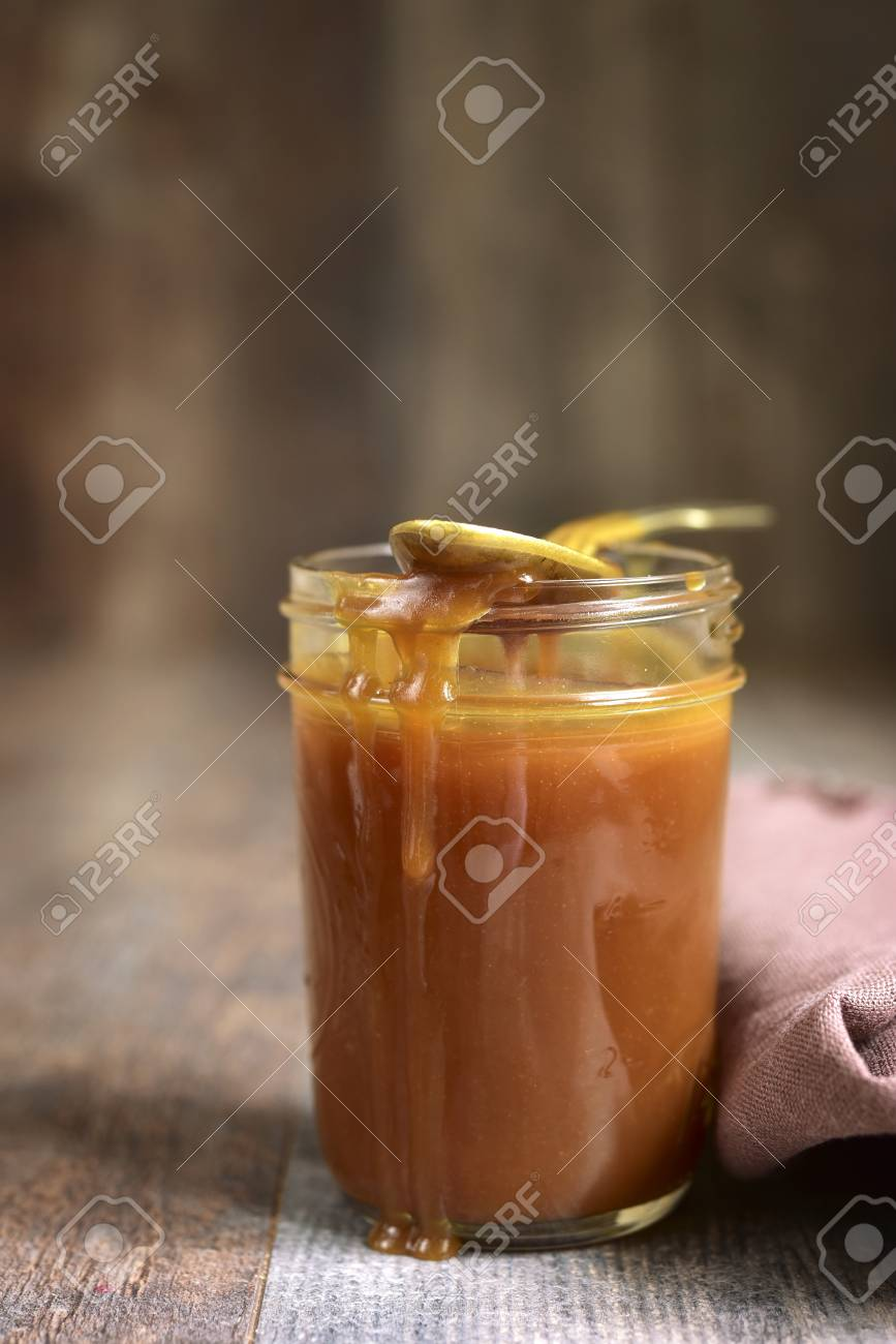 Homemade Melted Caramel In A Mason Jar On Rustic Background Stock Photo