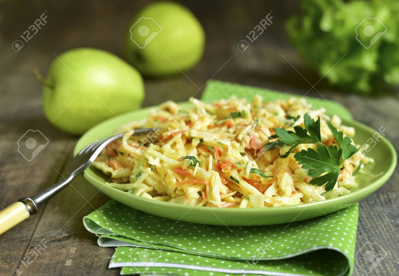 Coleslaw with apple on a green plate on ruatic background. - 58468575