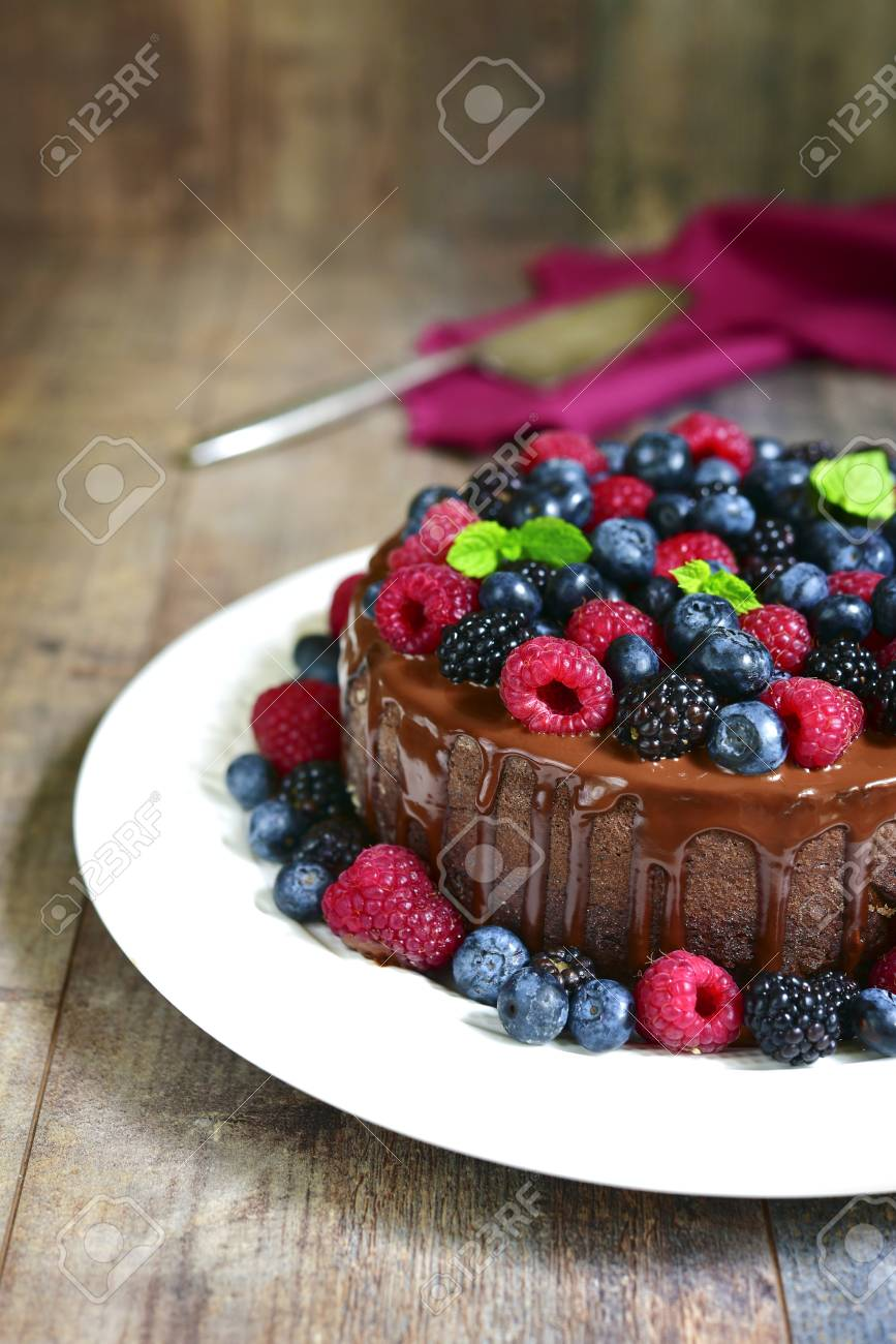 Chocolate Cake With Fresh Forest Berries And Glaze On Rustic Wooden Background Stock Photo
