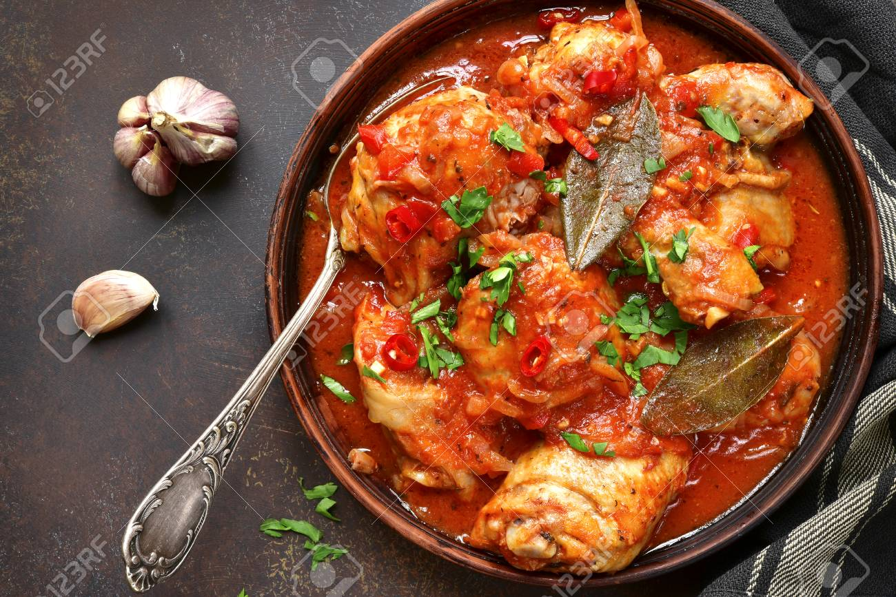 Chakhokhbili - chiken stew with cilantro (parsley) in tomato sauce in a clay bowl,traditional dish of georgian cuisine.Top view with copy space. - 74183065