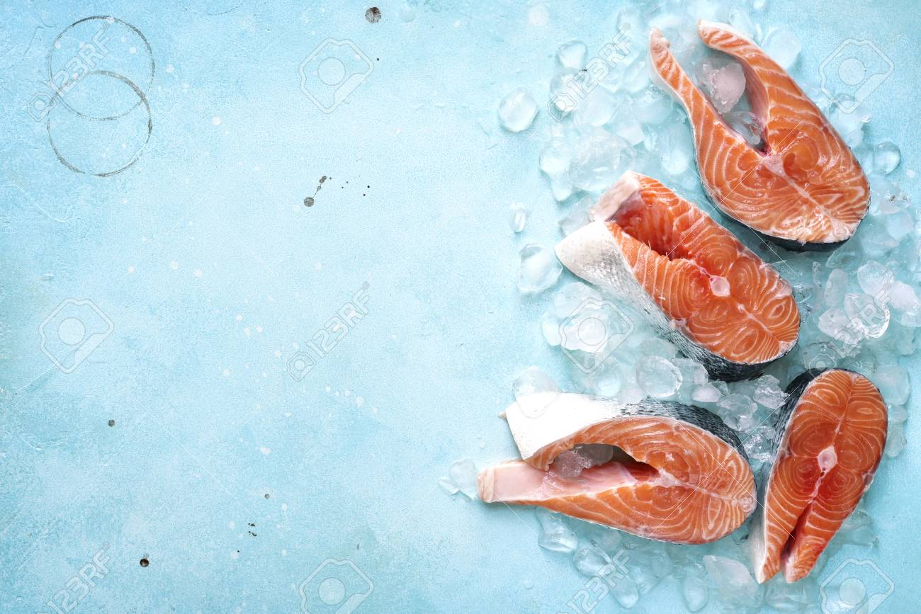 Steaks of raw salmon on ice on a blue slate,stone or metal background.Top view with space for text. - 81212063