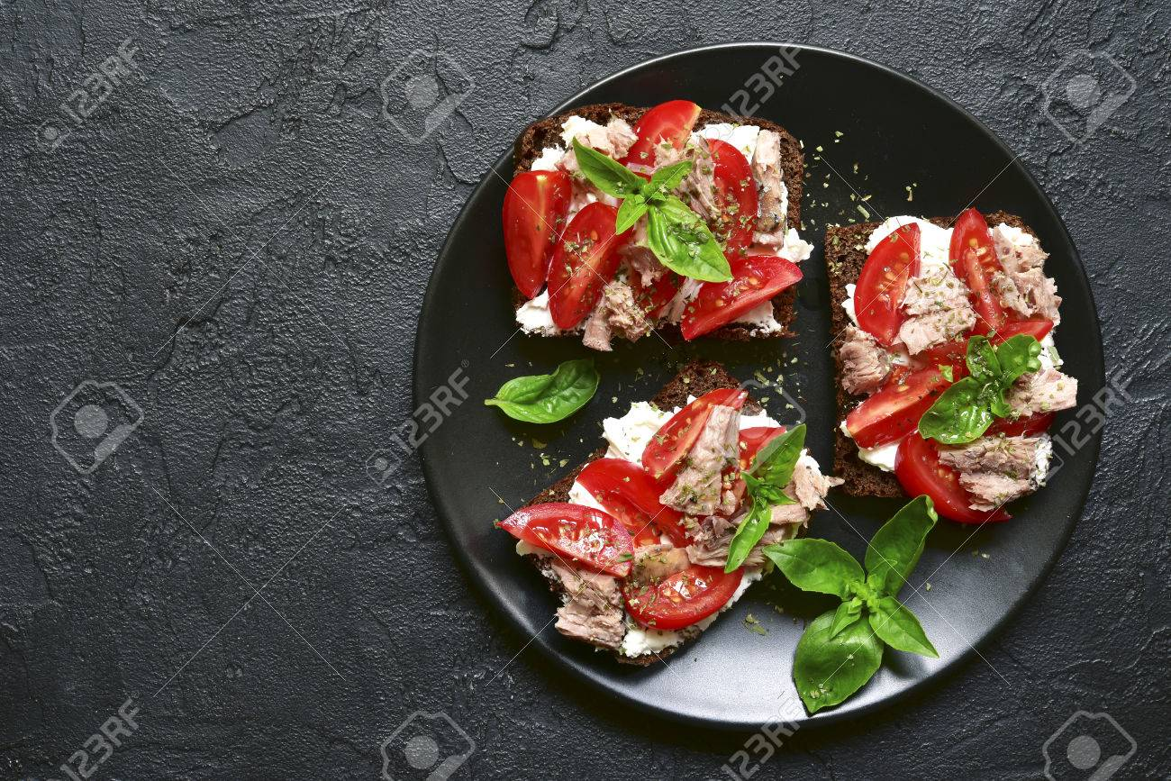 Rye sandwich with tomato,feta and tuna fillet on a black plate over dark slate,stone or concrete background.Top view with space for text. - 85702616