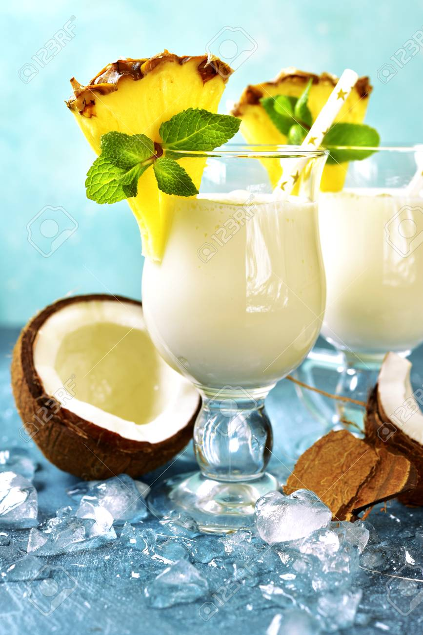 Traditional caribbean cocktail pina colada in a glasses on a blue slate,stone or concrete background. - 90005334