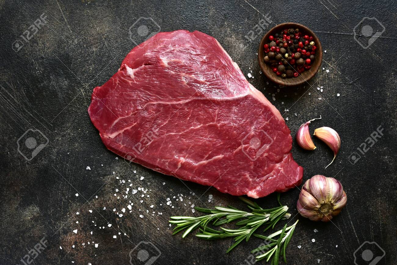 Raw beef steak with spices on a dark slate, stone or concrete background. Top view with copy space. - 129922843