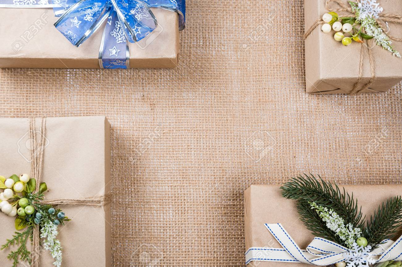 classy christmas gifts box presents in brown paper with bow and new year decor on burlap
