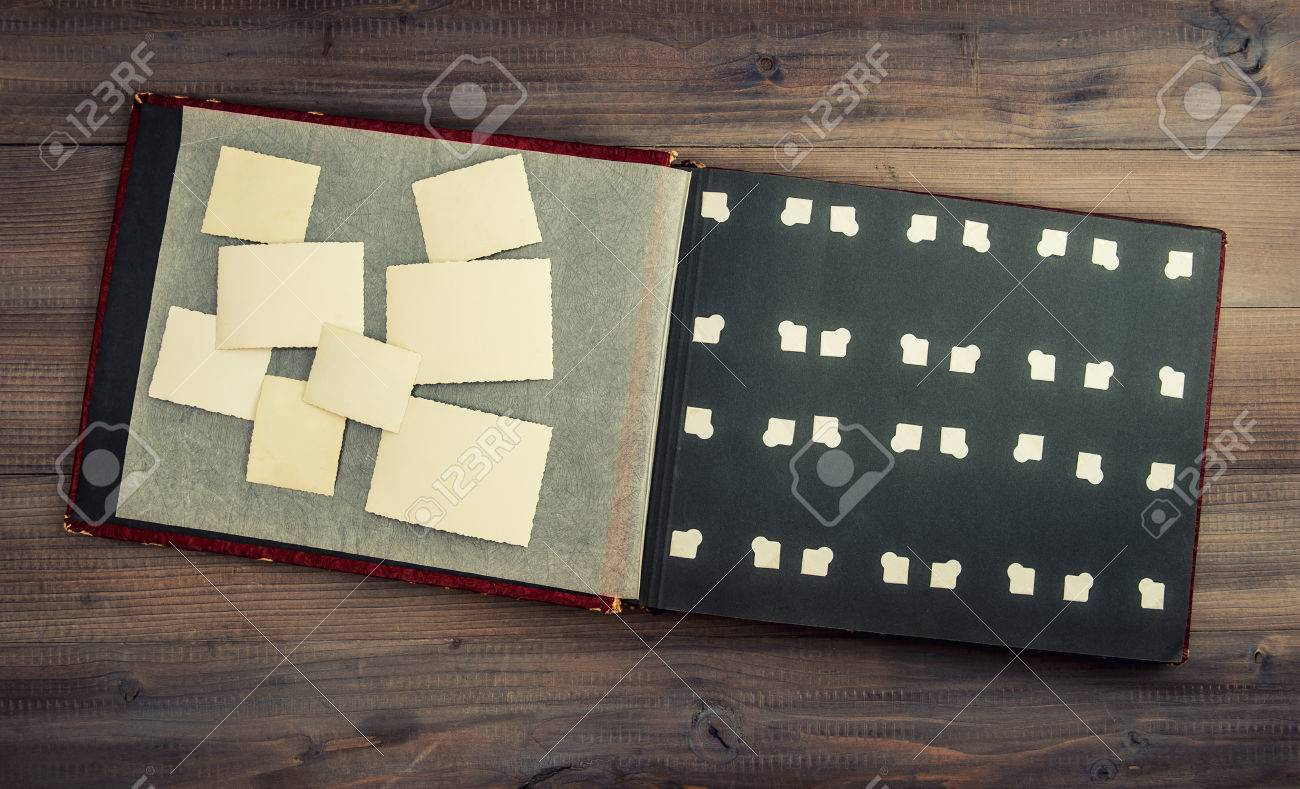 antique album with photos on wooden table vintage style
