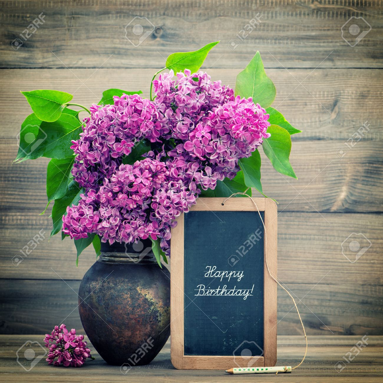 Bouquet of lilac flowers on wooden blackboard with sample text bouquet of lilac flowers on wooden blackboard with sample text happy birthday retro style toned picture izmirmasajfo