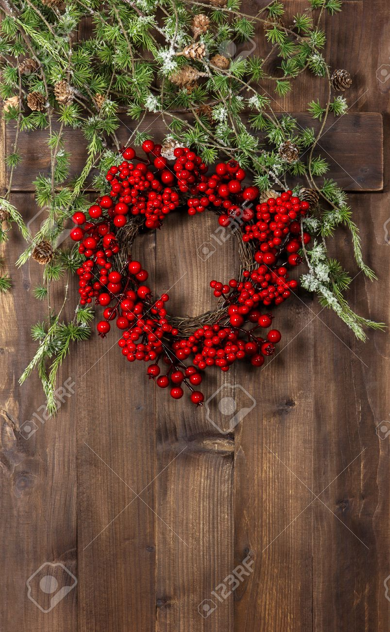 Green Christmas Tree Branches And Wreath From Red Berries Over Rustic Wooden Background Festive Decoration