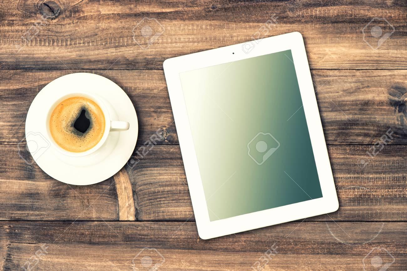 Tablette pc et café sur le bureau en bois banque d images et