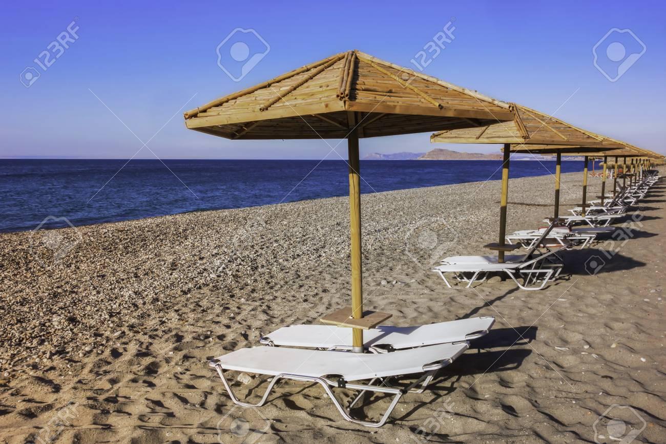 Row Of Bamboo Beach Umbrellas With Sunbeds On Empty Beach