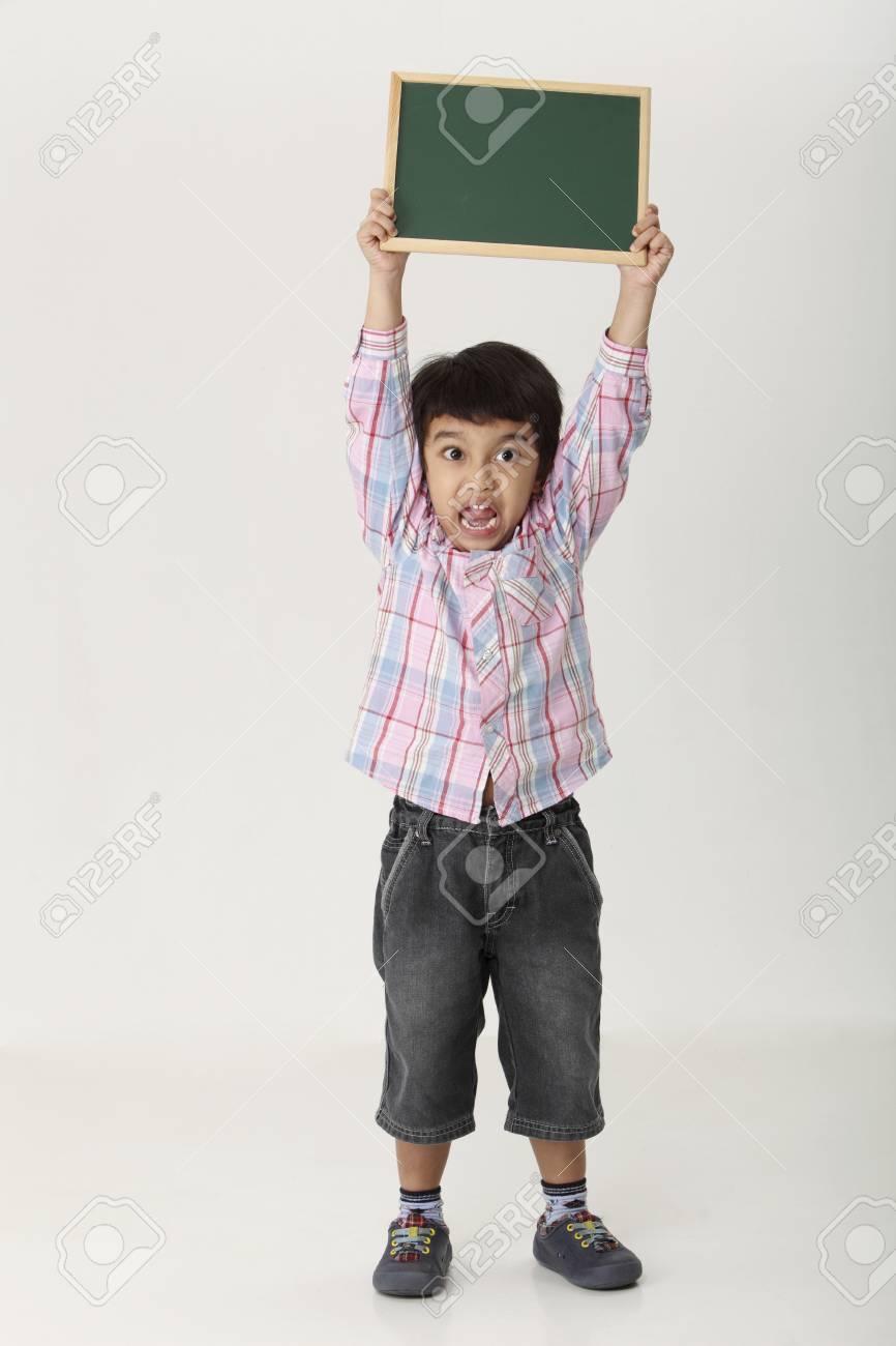 boy holding a blank black board - 119228240