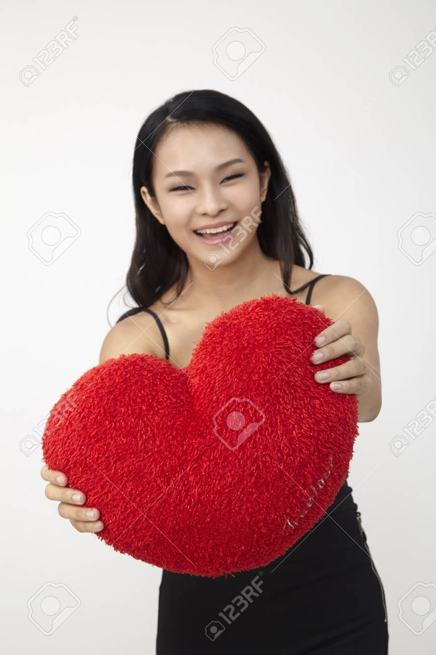 Asian woman holding a red heart-shaped pillow. - 120967988