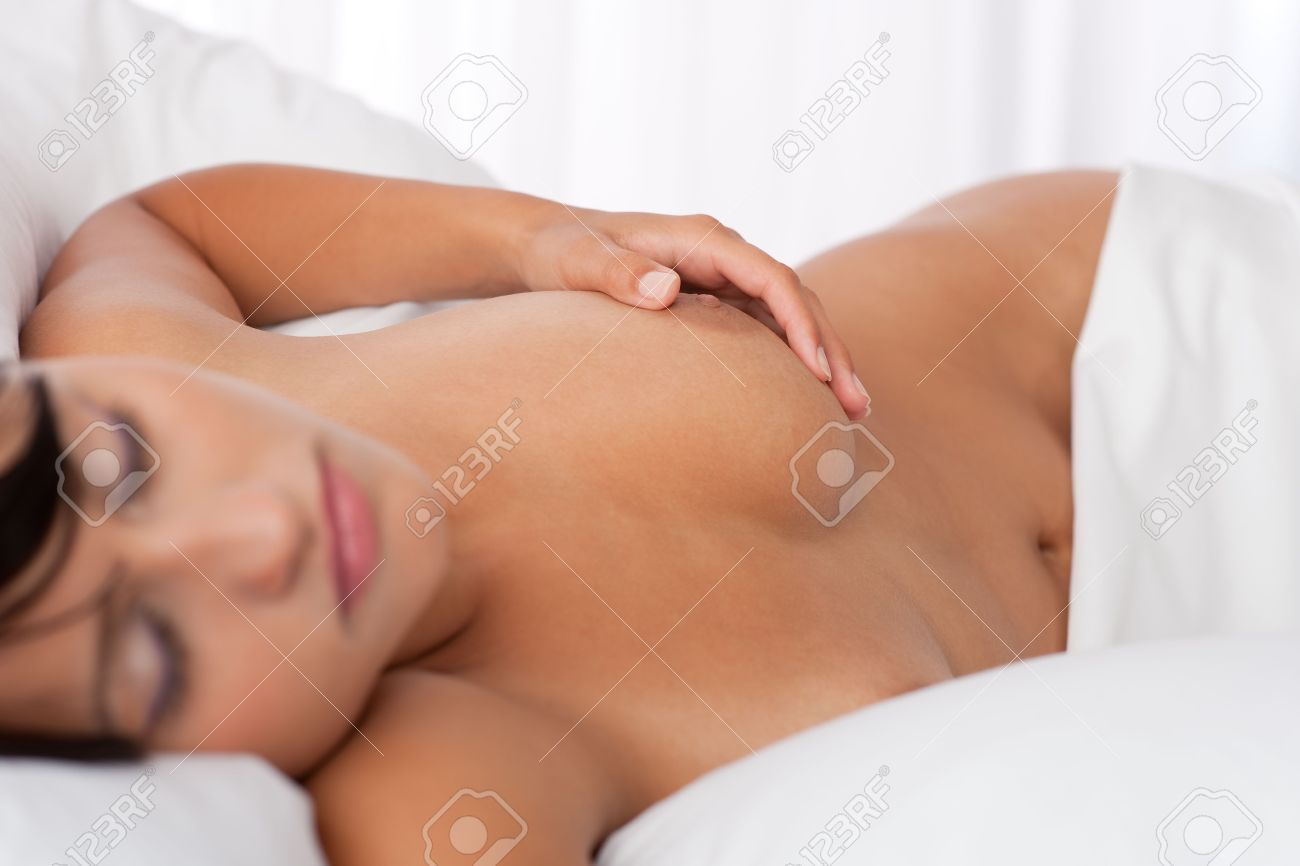 Young woman lying naked in white bed, focus on nipple, shallow DOF Standard-Bild - 5383799