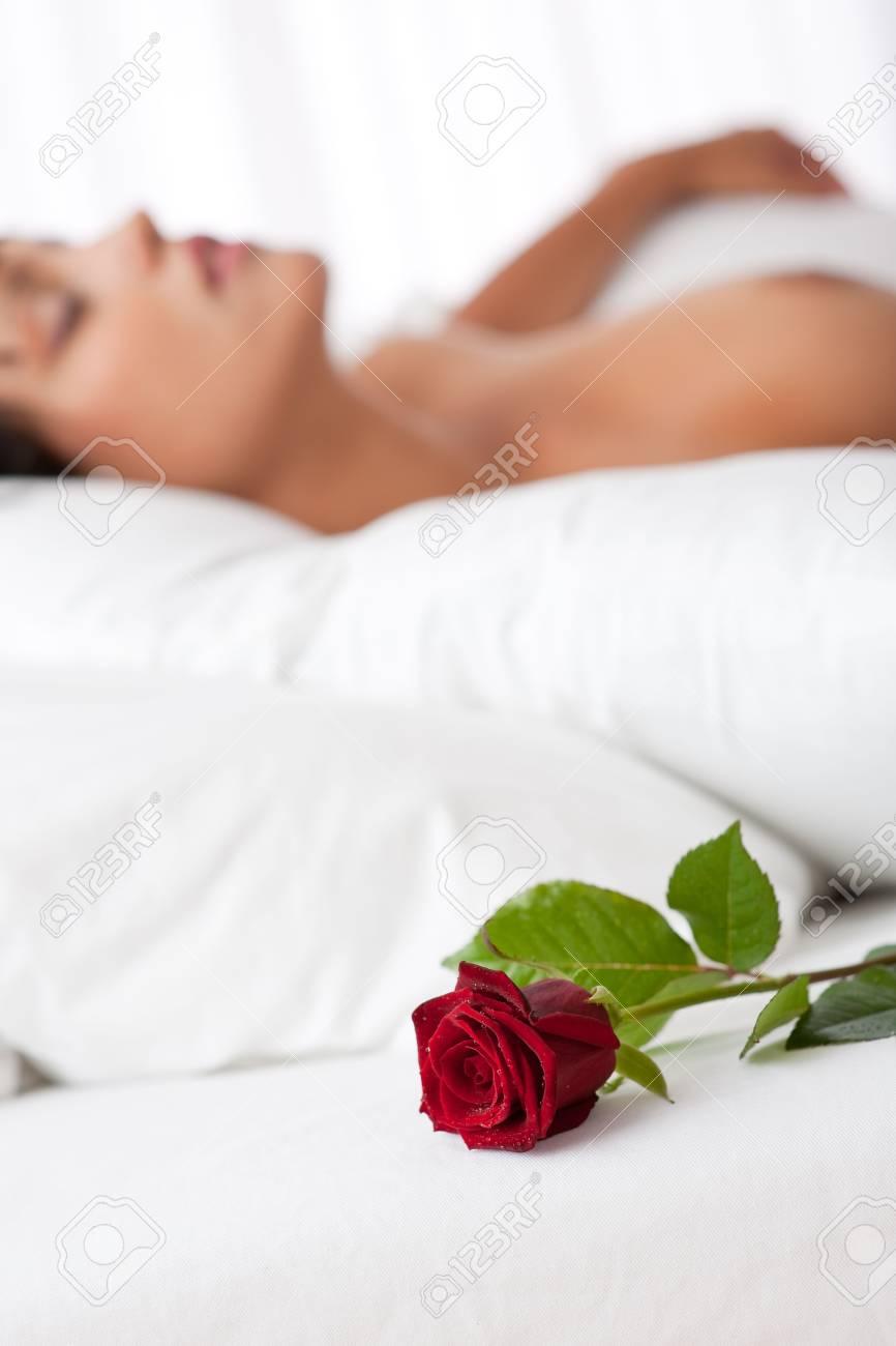 Woman lying in white bed, focus on rose, shallow DOF Standard-Bild - 5383832
