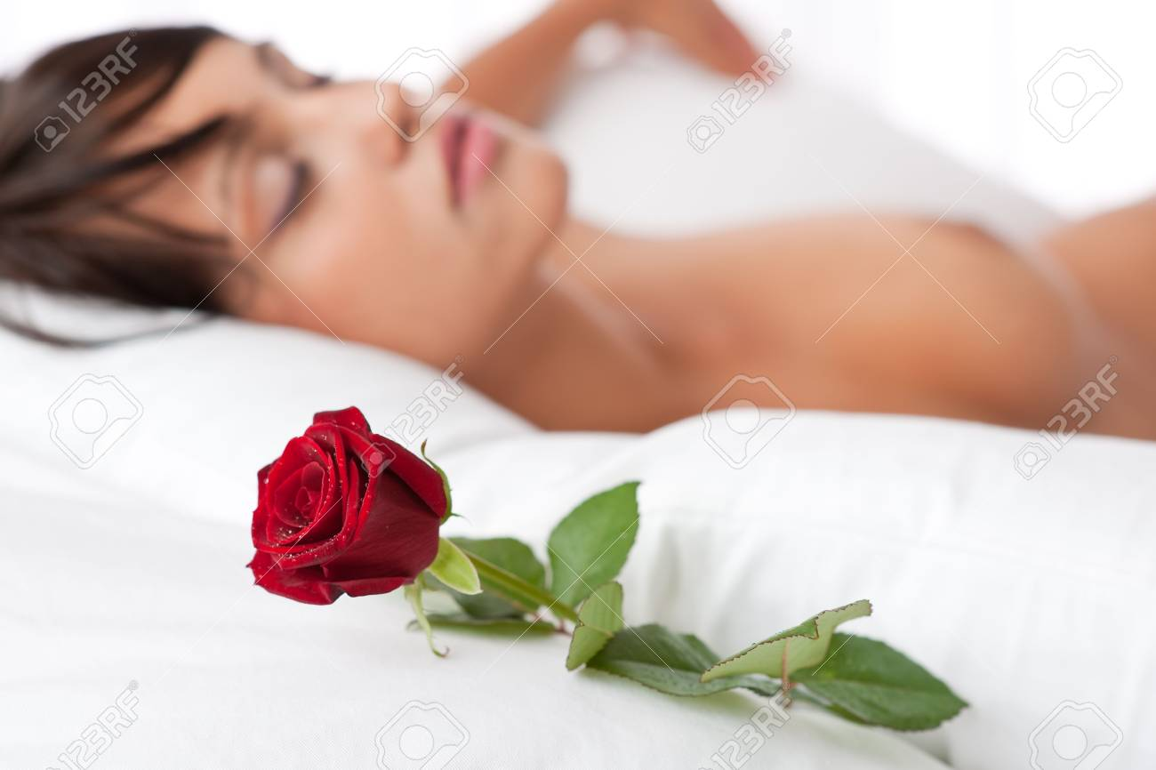 Woman lying in white bed, focus on rose, shallow DOF Standard-Bild - 5383807
