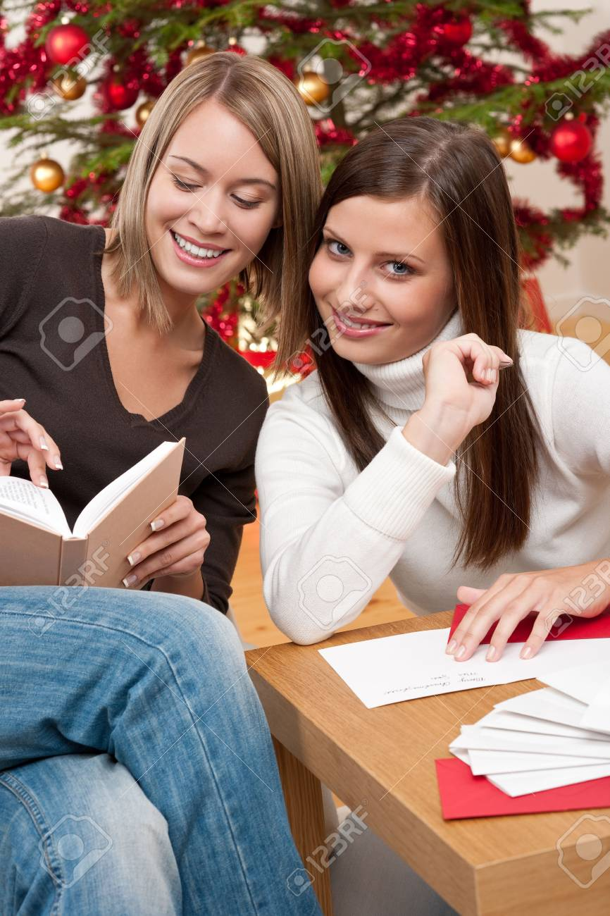 Two young women writing Christmas cards in front of tree Stock Photo - 5712900
