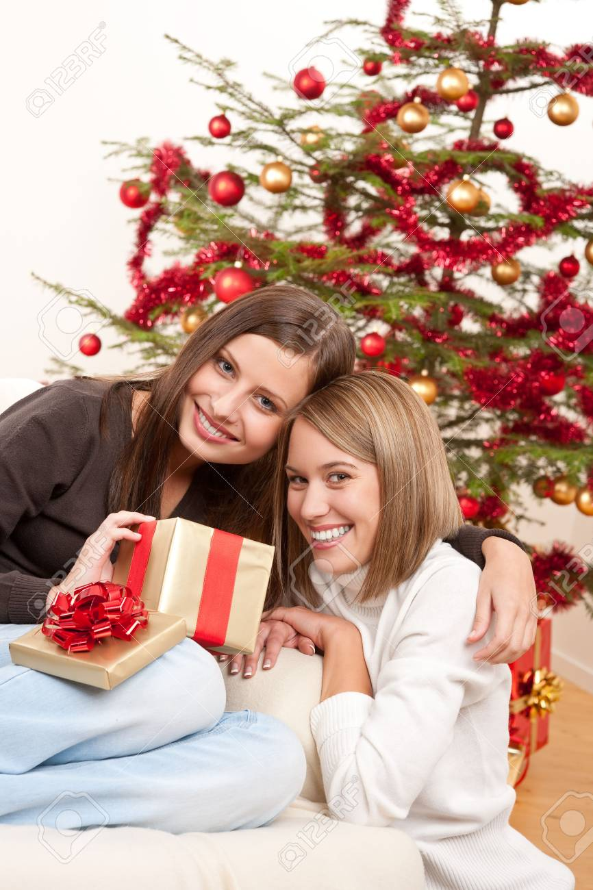 Two smiling women with Christmas present in front of tree Stock Photo - 5712850