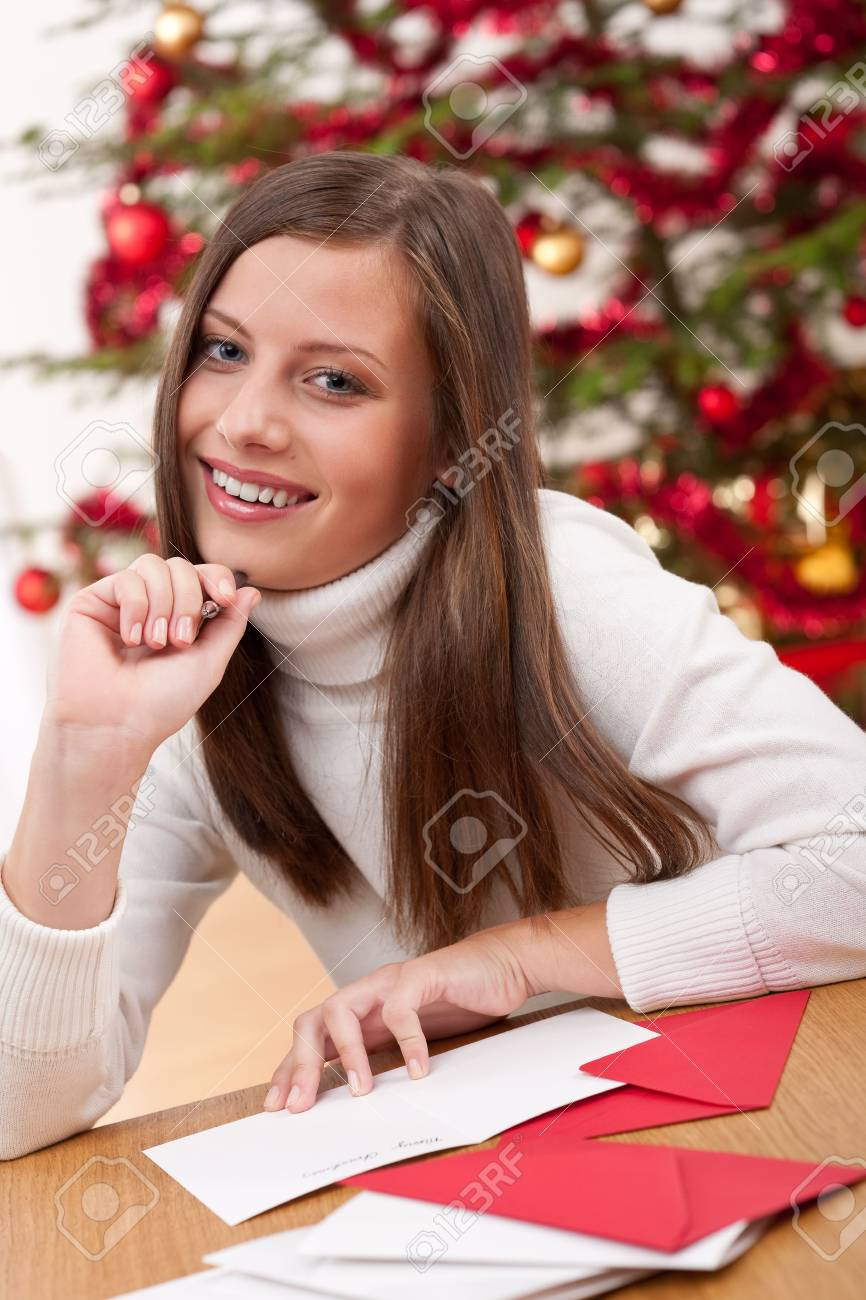 Young woman writing Christmas card in front of tree Stock Photo - 5714167
