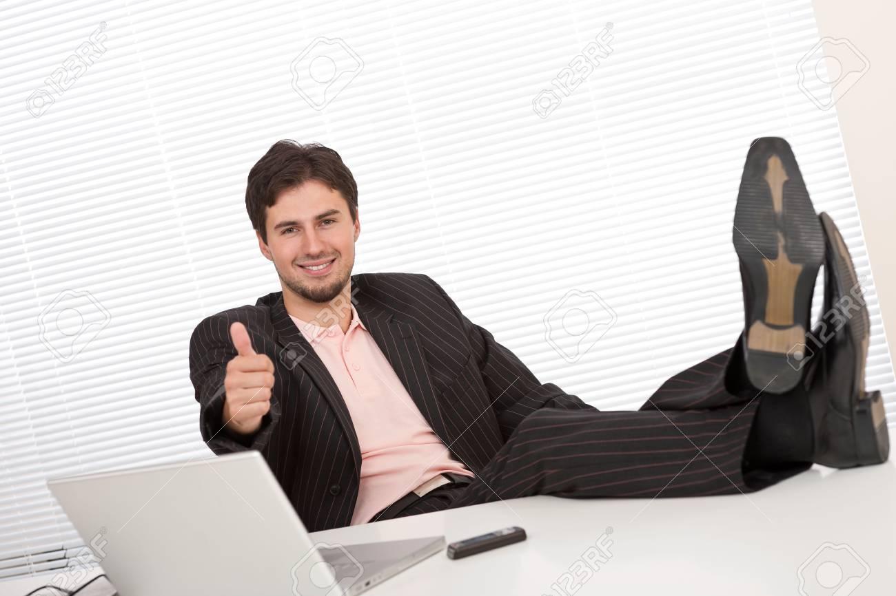 Young businessman gesturing at office having legs up Standard-Bild - 5797076