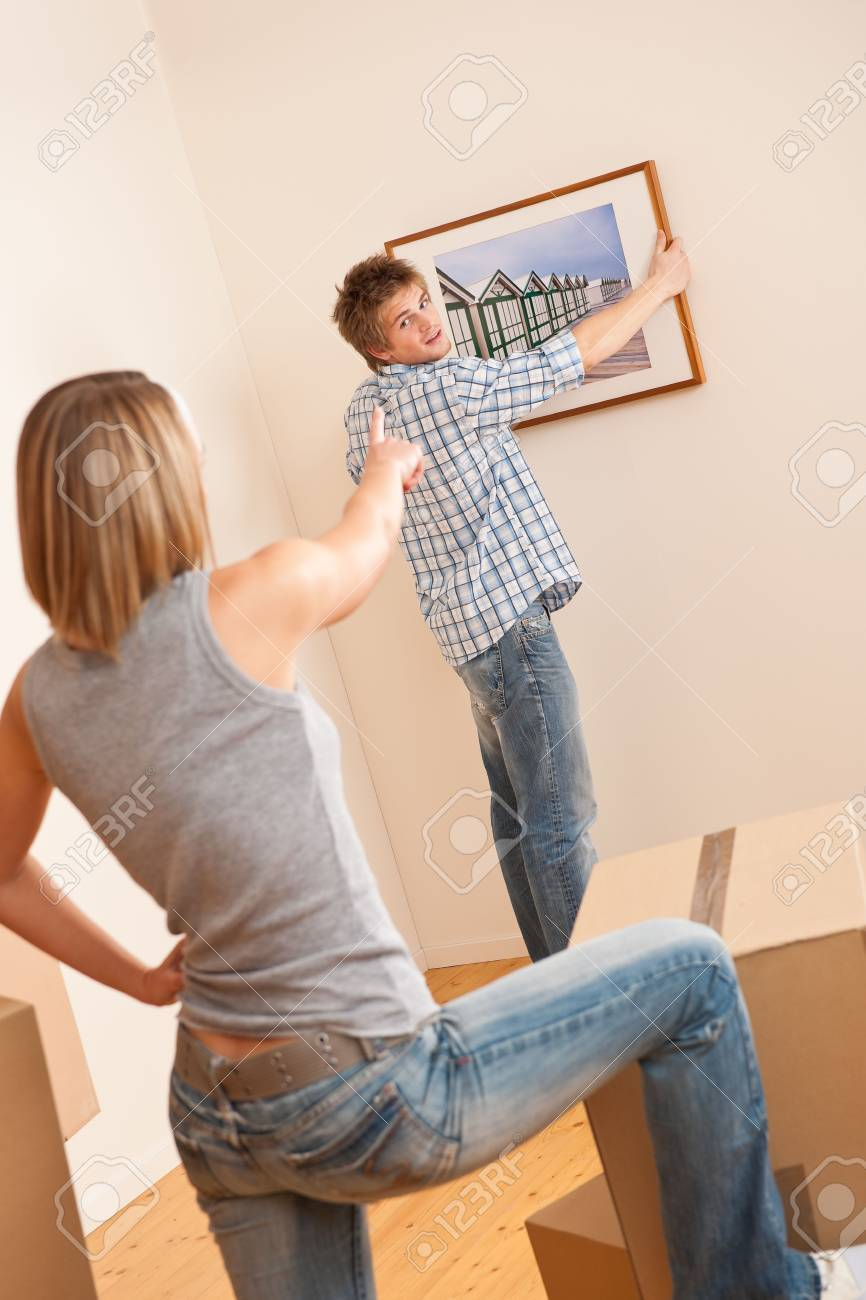 Moving house: Couple hanging picture on wall in new home Stock Photo - 6052898