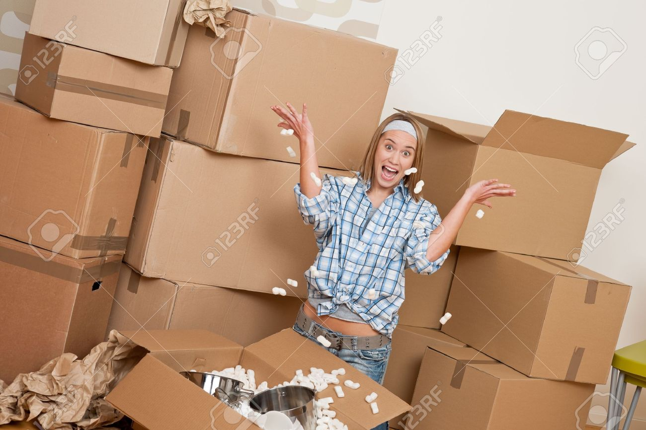 Moving house: Happy woman unpacking box in new home, kitchen, pots and pans Stock Photo - 6048996