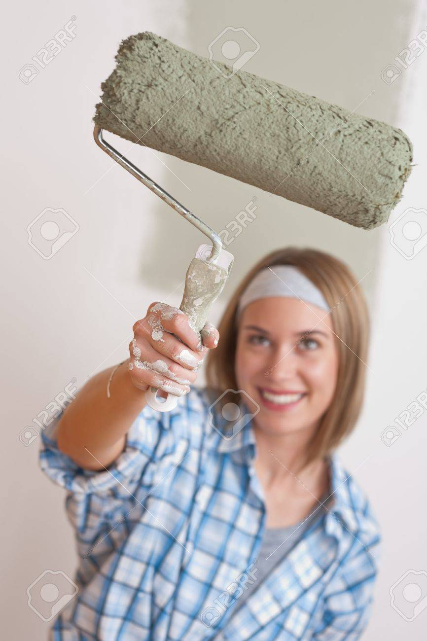 Home improvement: Smiling woman with paint roller painting wall Stock Photo - 6106905