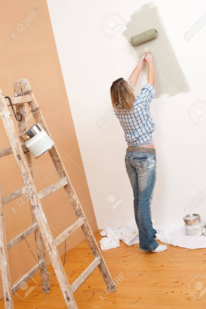 Home improvement: Cheerful woman with paint roller and ladder painting wall Stock Photo - 6220924