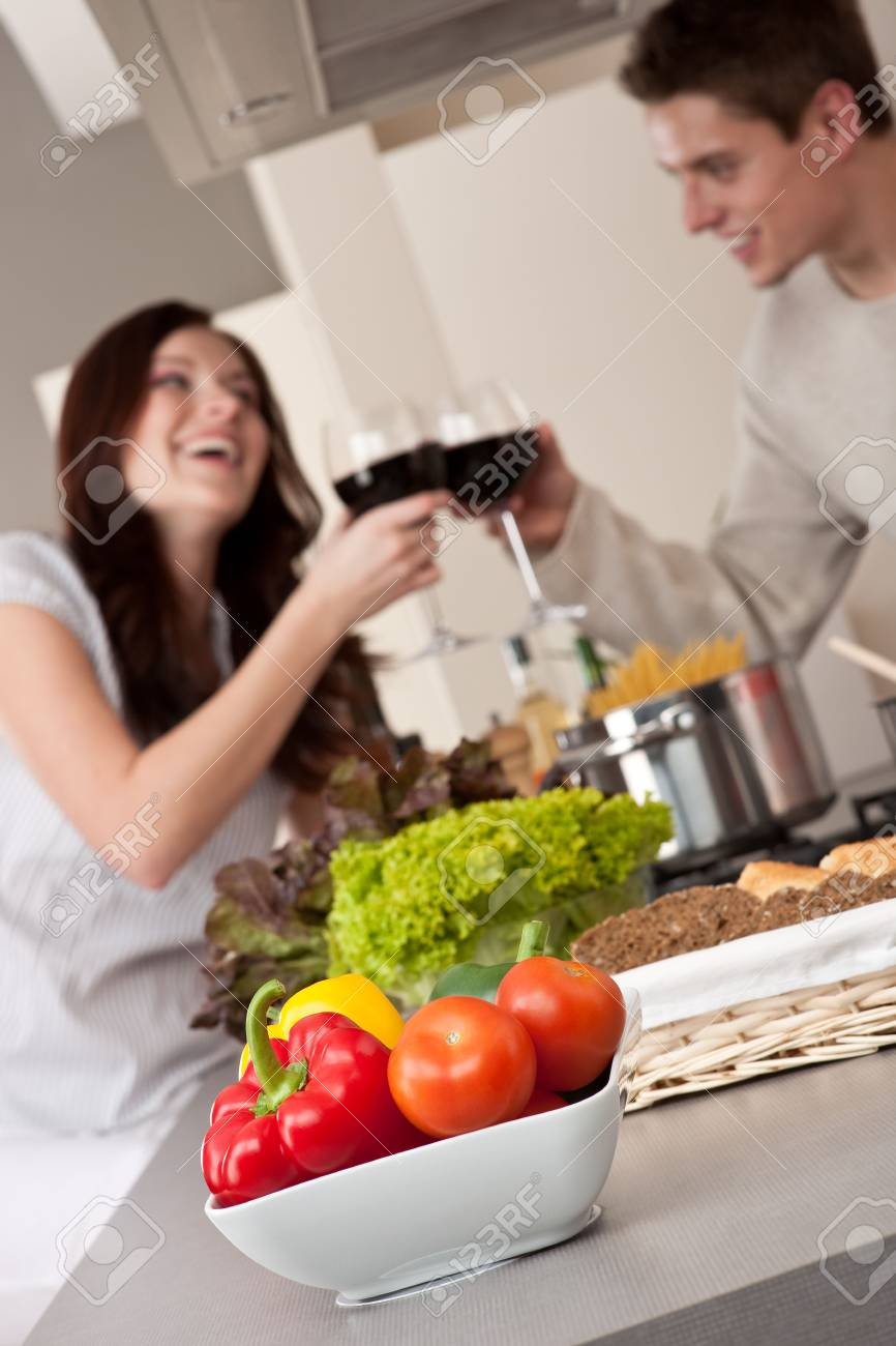 Young couple drinking red wine in kitchen, focus on bowl with vegetable Stock Photo - 6418698