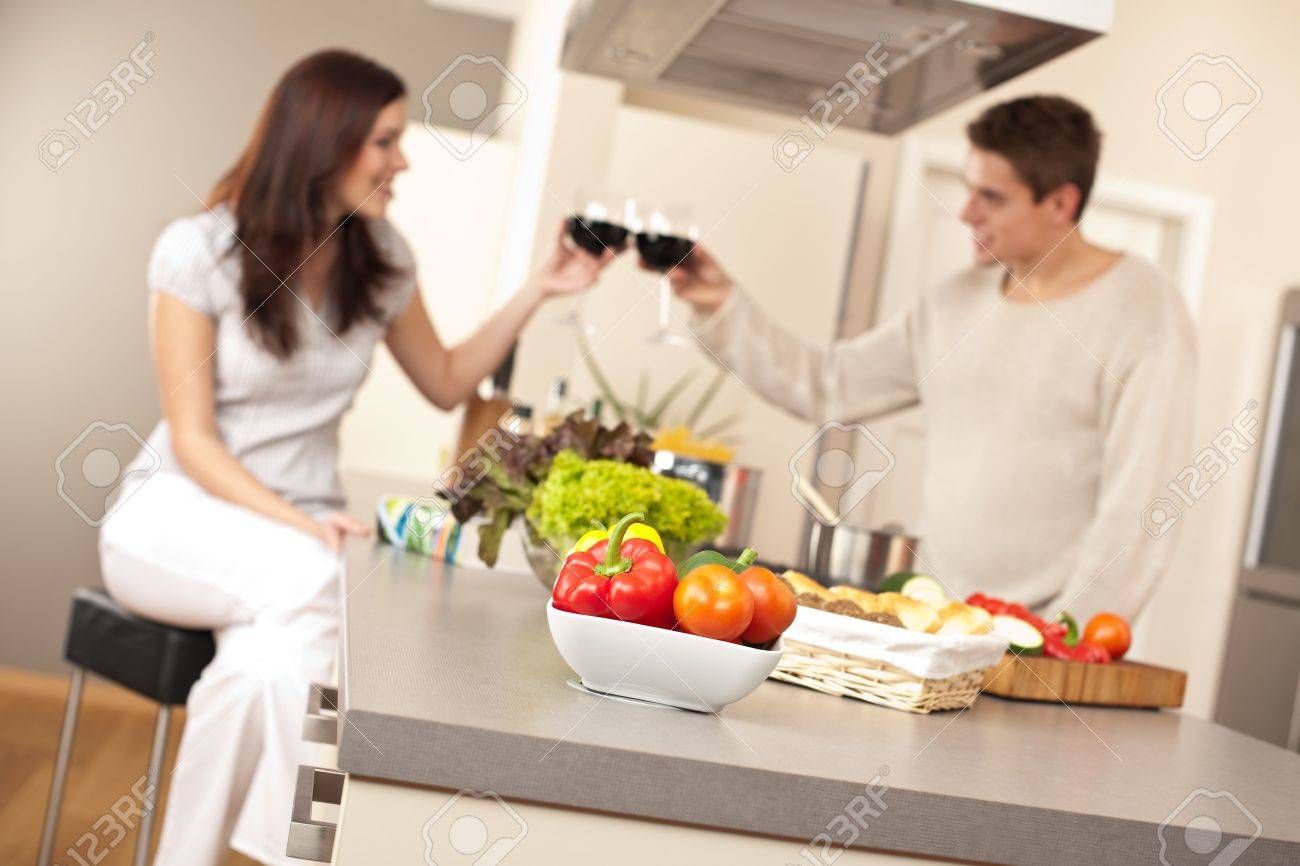 Young couple drinking red wine in kitchen, focus on bowl with vegetable Stock Photo - 6418699