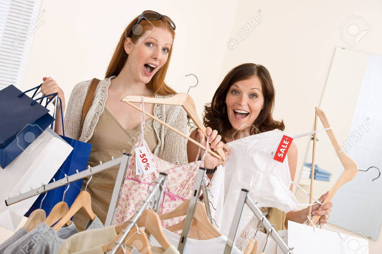 Fashion shopping -  Two happy young woman choose clothes in shop holding shopping bag Stock Photo - 7169757