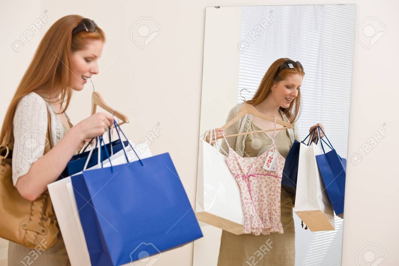 Fashion shopping - Happy woman choose sale clothes, holding shopping bag in mirror Stock Photo - 7169733