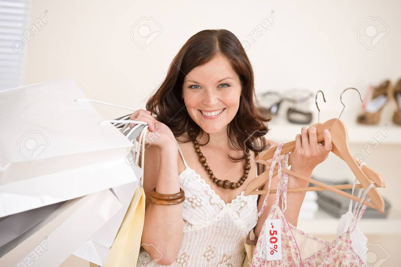 Fashion shopping - Happy woman choose sale clothes, holding shopping bag Stock Photo - 7169729