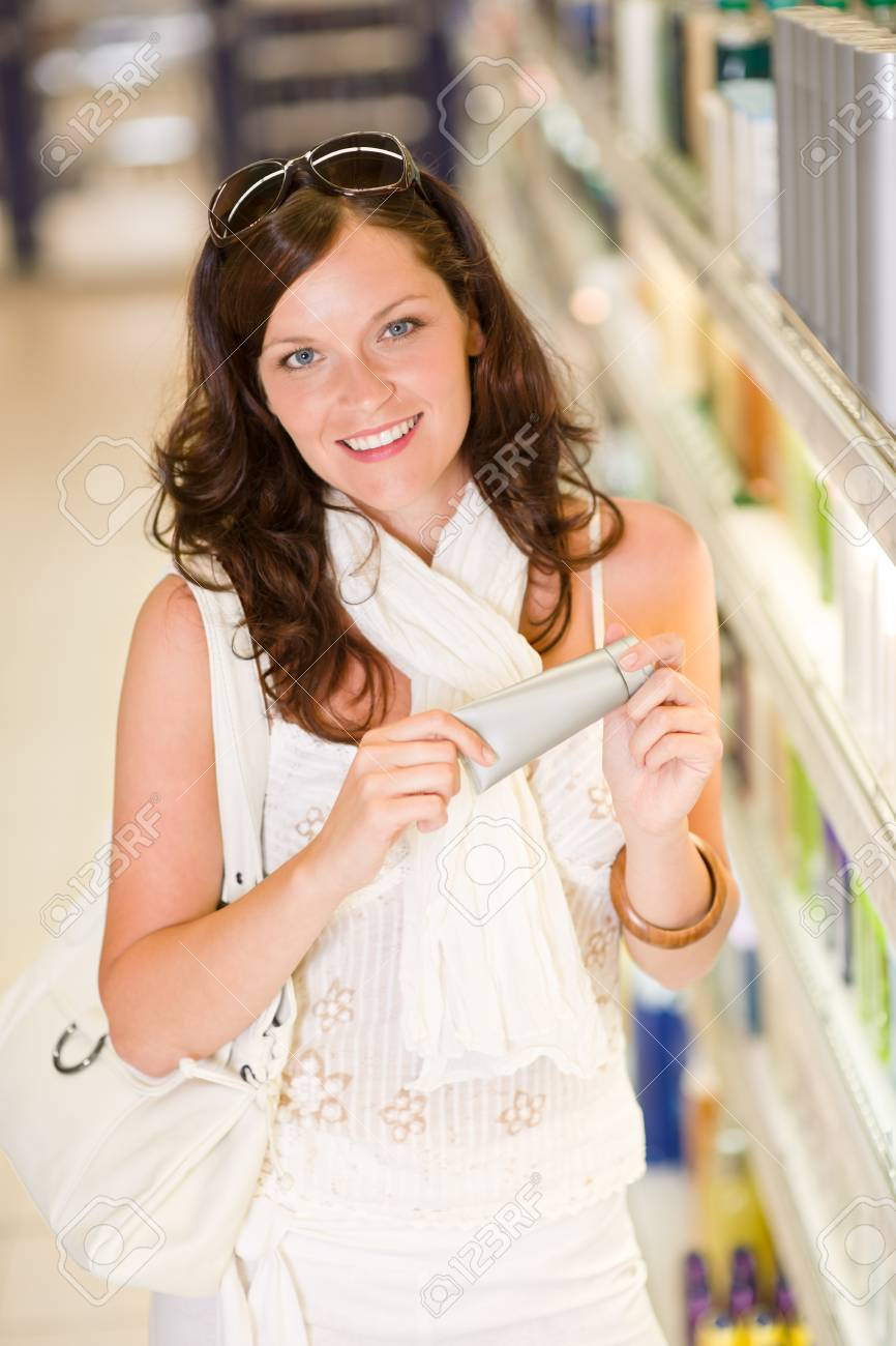 Shopping - smiling woman holding moisturizer in supermarket Stock Photo - 7218817