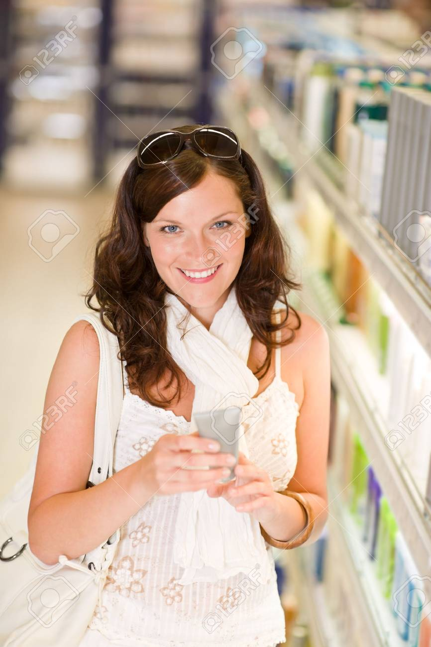 Shopping - smiling woman holding moisturizer in supermarket Stock Photo - 7218829