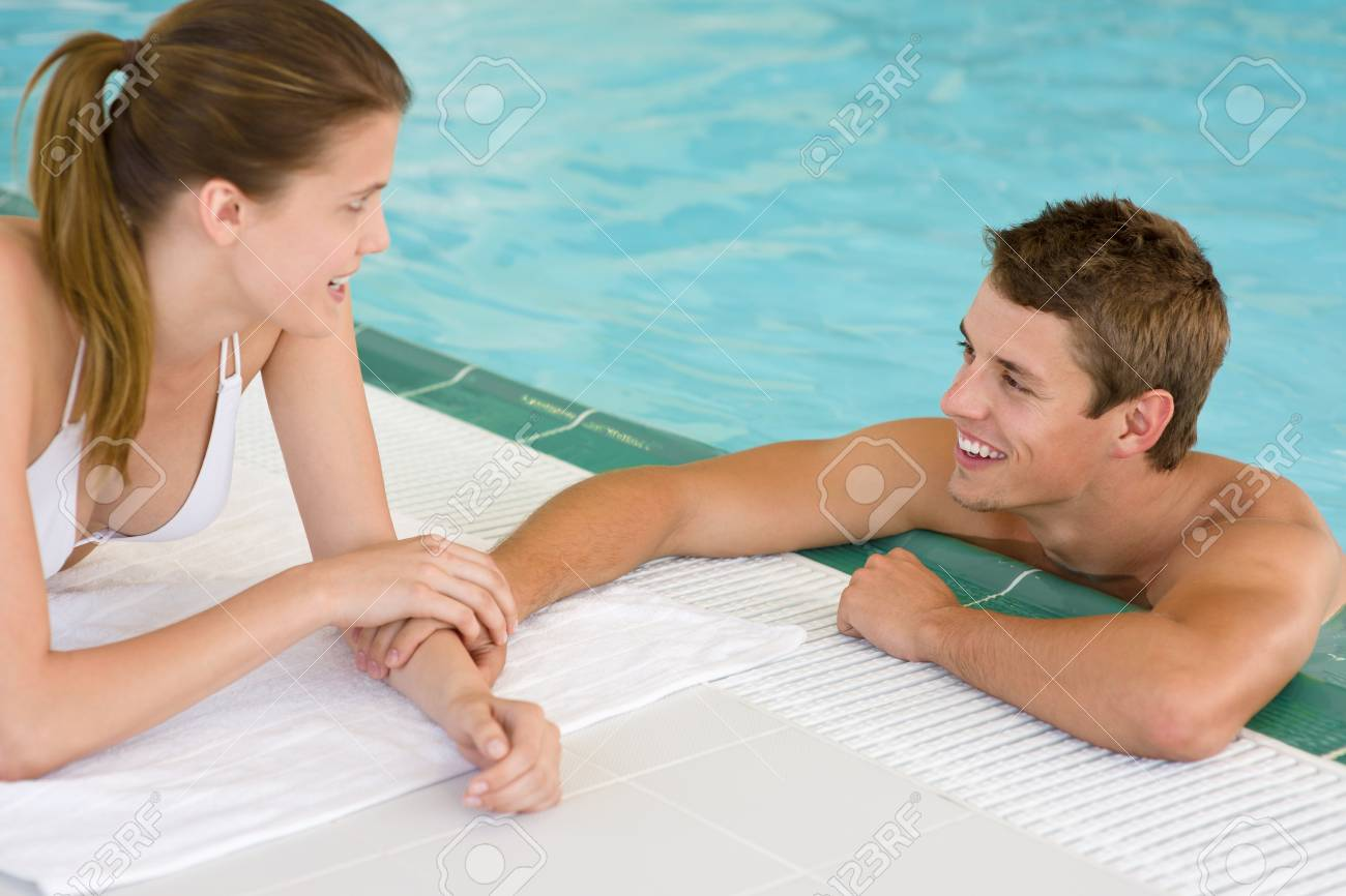 Swimming pool - young loving couple hold hands on poolside Stock Photo - 7368657