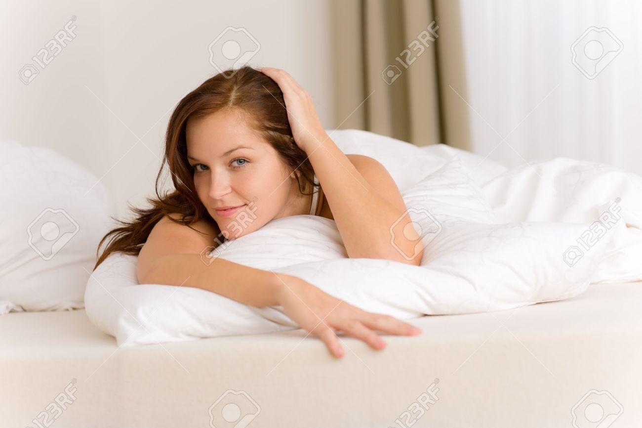 Chambre à coucher   femme heureuse dans le lit de couleur blanche ...