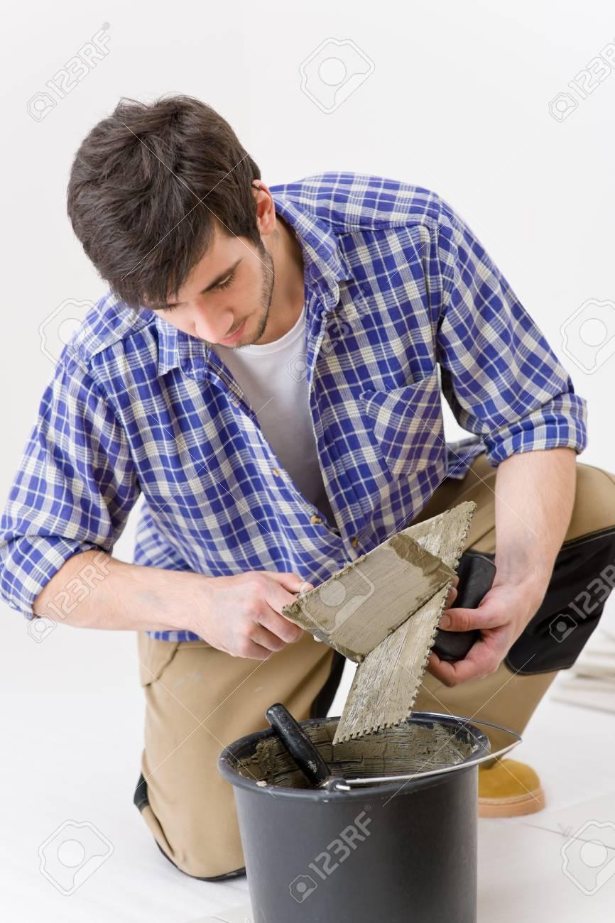 Home improvement, renovation - handyman laying tile, trowel with mortar Stock Photo - 8374818
